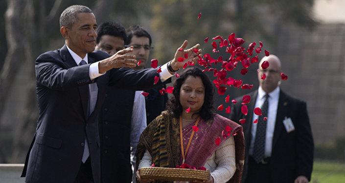President Barack Obama throws rose petals as he participates in a wreath laying ceremony at the Raj Ghat Mahatma Gandhi Memorial, New Delhi, India, Sunday, Jan. 25, 2015