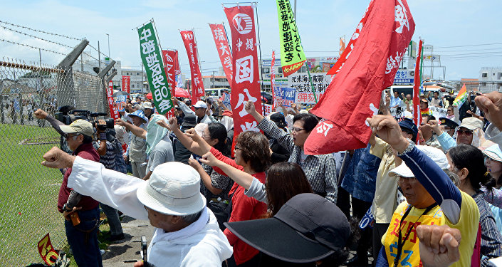 People raise their fists as they shout slogans to protest against the US military presence in front of the US Kadena Air Base in Cyatan, Okinawa prefecture, on May 21, 2016