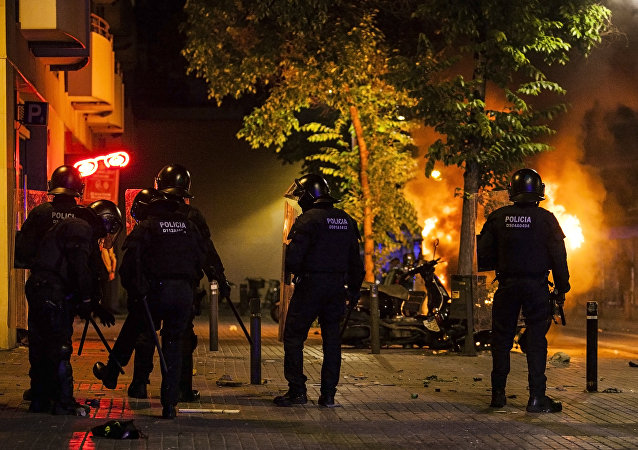 Police officers stand as a truck is ablaze during riots after a demonstration against the evacuation of an occupied old bank branch in Barcelona, on May 23, 2016