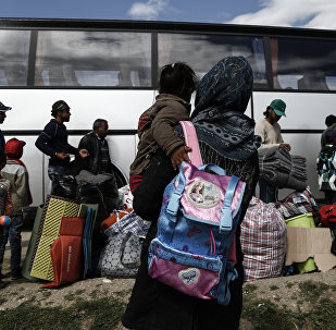 Refugees stand near a bus as they wait to be transferred to a hospitality centre during a police operation at a refugee camp at the border between Greece and Former Yugoslav Republic of Macedonia (FYROM), near the village of Idomeni, northern Greece,on May 25, 2016