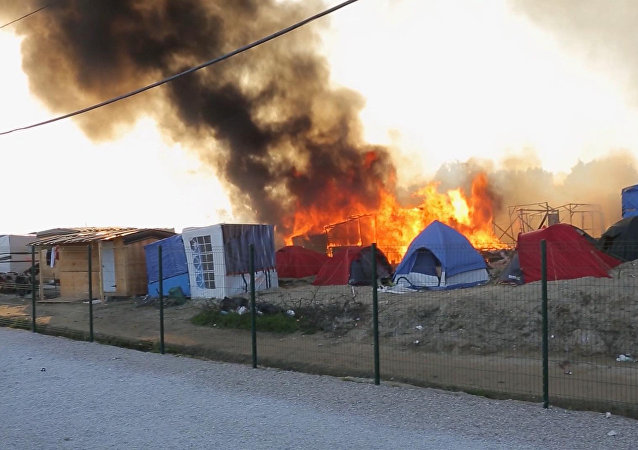 Smoke rises from the huts and tents set on fire during clashes between migrants, at a makeshift camp, in Calais, France, Thursday, May 26, 2016