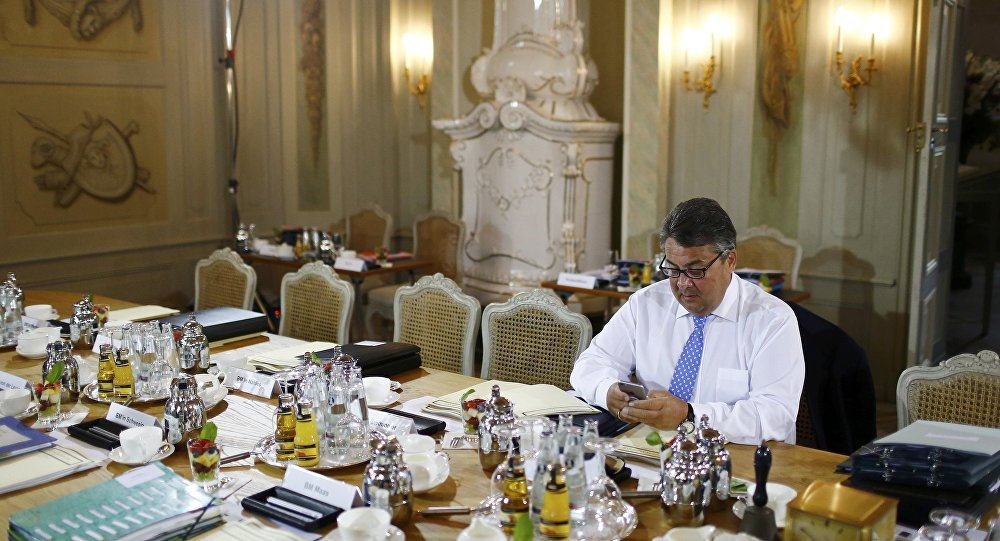 German Economy Minister Sigmar Gabriel checks his phone before a cabinet meeting at the German government guesthouse Meseberg Palace, Germany, May 25, 2016