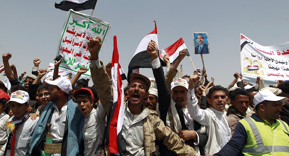 Yemenis shout slogans and wave national flags as they take part in celebrations marking the 26th anniversary of Yemen's 1990 reunification in the capital Sanaa on May 22, 2016