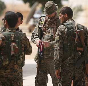 A US fighter, who is fighting alongside with Syria Democratic Forces (SDF), carries his national flag as he stands with SDF fighters in northern province of Raqqa, Syria May 27, 2016