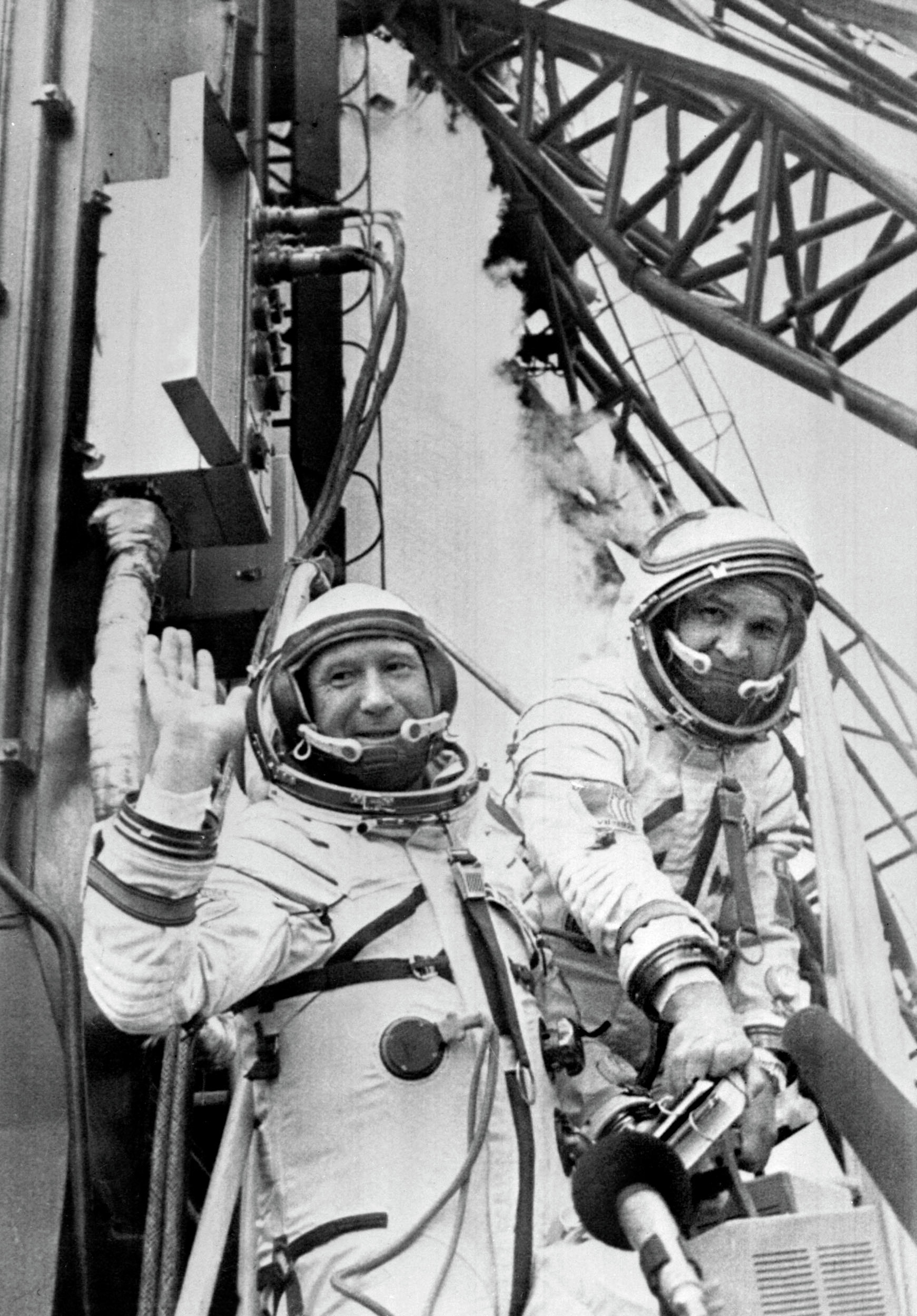Russian cosmonauts commander Alexei Leonov (L) and V. Kubasov wave to the people while getting in their spaceship Soyuz ready to be launched 15 July 1975 from Baïkonour