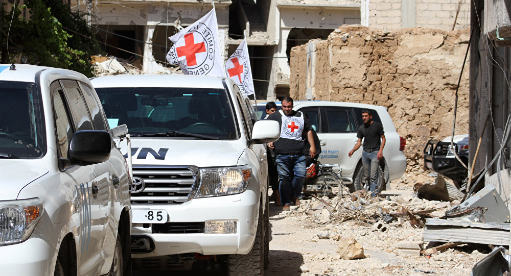 Vehicles of the International Committee of the Red Cross (ICRC) and the United Nations wait on a street after an aid convoy entered the rebel-held Syrian town of Daraya, southwest of the capital Damascus, on June 1, 2016