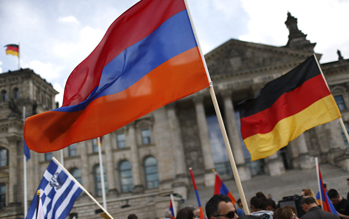 Rally participants wave Armenian and German flags in front of the Reichstag, the seat of the lower house of parliament Bundestag in Berlin, Germany, June 2, 2016, as they protest in favor of the approval of a symbolic resolution by Germany's parliament declaring the 1915 massacre of Armenians by Ottoman forces a genocide