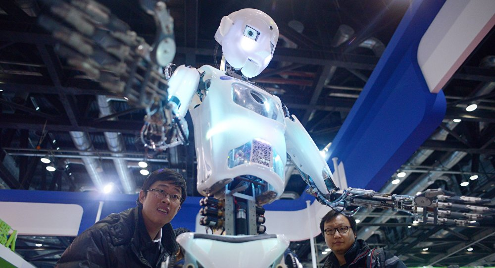 This picture taken on November 24, 2015 shows visitors watching a robot (C) demonstration during the World Robot Conference in Beijing