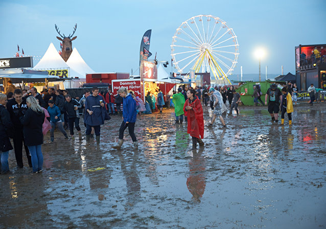 Visitors to the music festival Rock am Ring are seen wading through mud aafter a heavy downpour in the west German city of Mendig on June 3, 2016.
