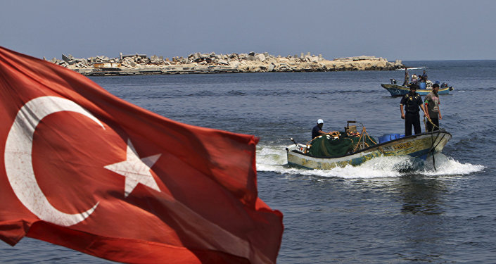 A Turkish flag hangs in the Gaza port as fishermen in their boats pass off the shore of Gaza City, Tuesday, Sept. 13, 2011