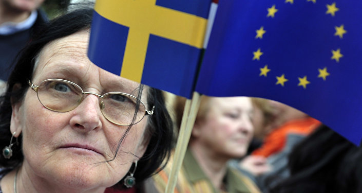 A woman holding a European flag and a Swedish flag