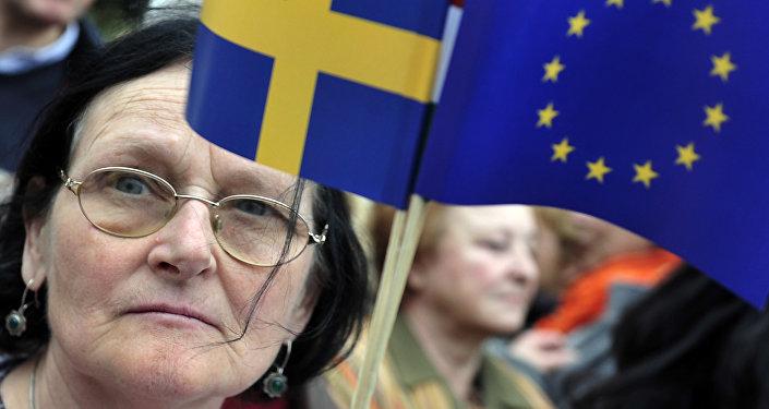 A woman holding a European flag and a Swedish flag