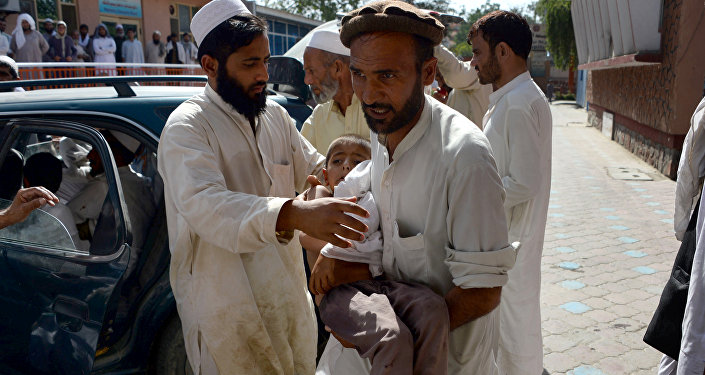 An Afghan volunteer carries a wounded child following an explosion inside a mosque in the Rodat district of Nangarhar province on June 10, 2016