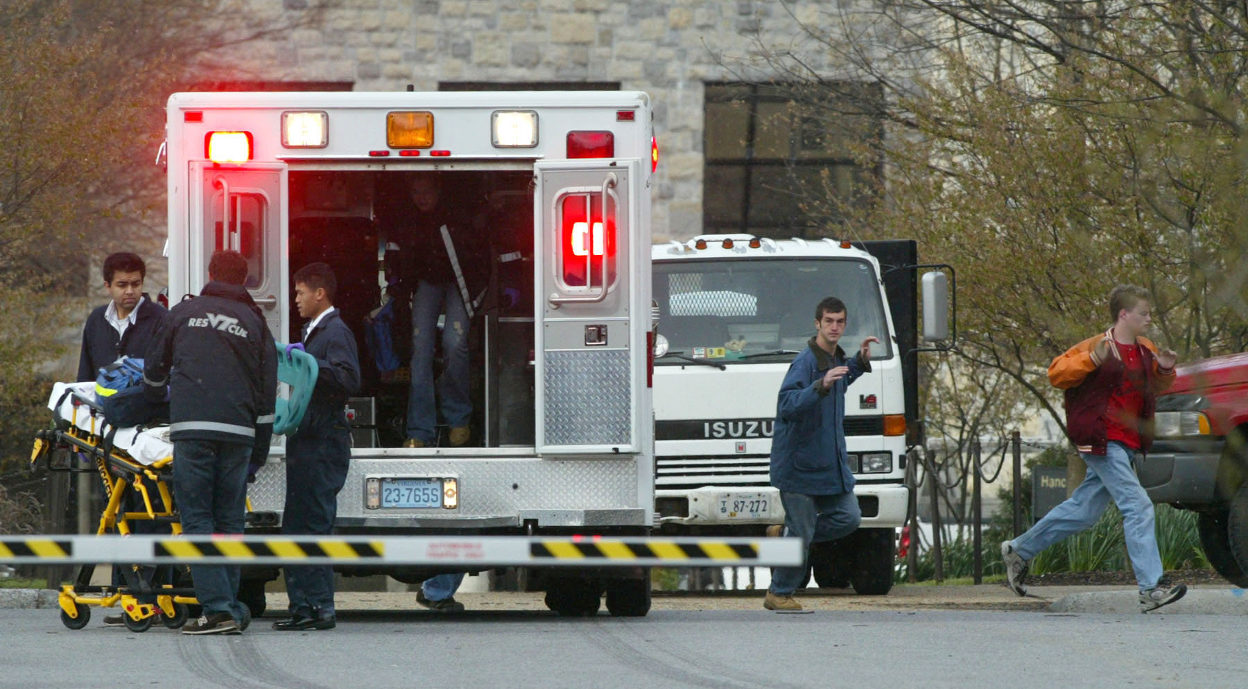 Virginia Tech students run from Norris Hall as an ambulance crew arrives on the scene in Blacksburg, Va., Monday, April 16, 2007