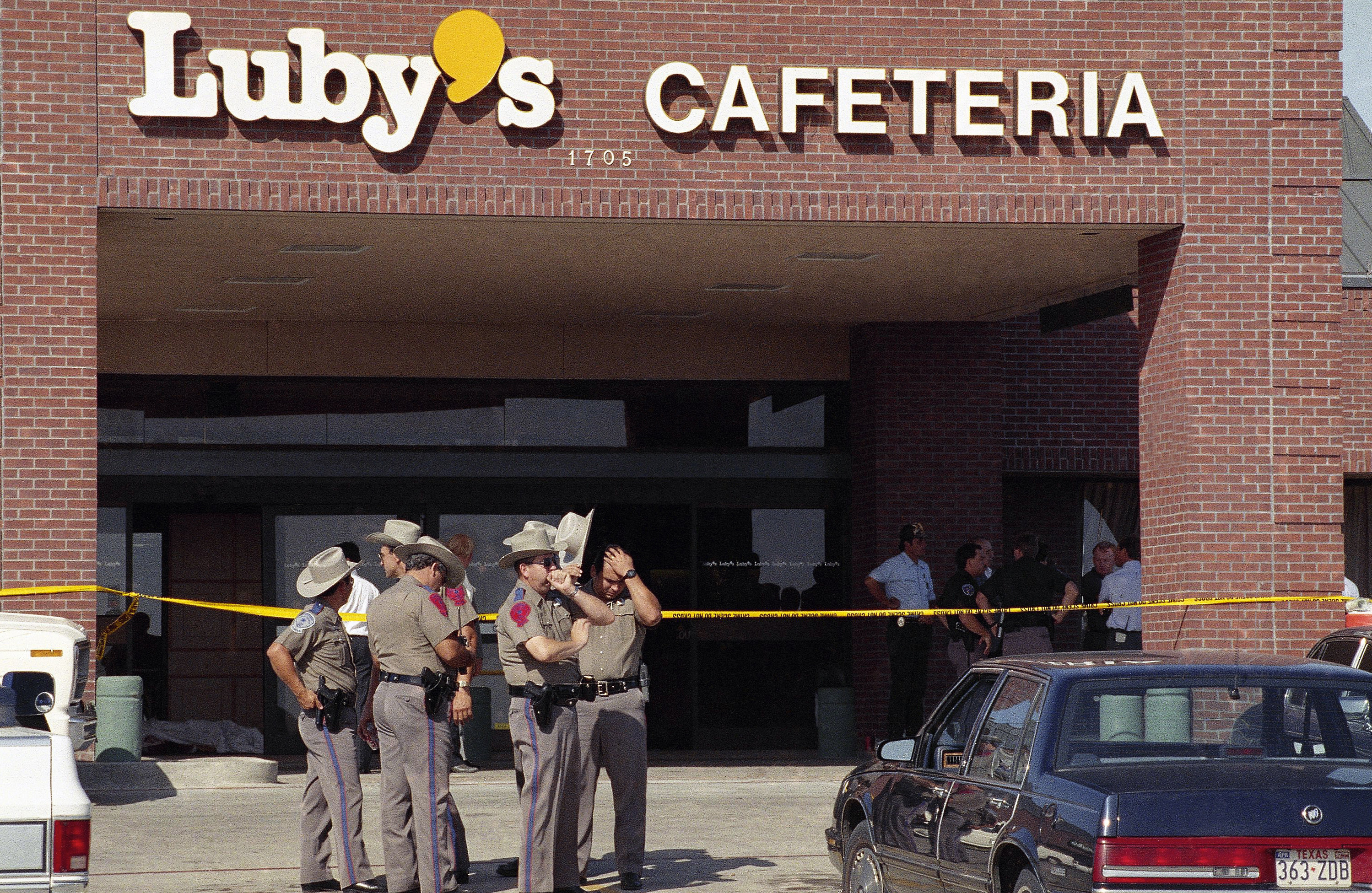 Police officers gather outside Luby's Cafeteria in Killeen, Texas, at the scene where a gunman killed 23 people including himself, with semi-automatic gunfire during lunchtime on Wednesday, Oct. 16, 1991