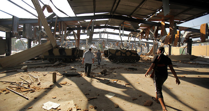 Libyan rebels walk at the Salaheddin army barracks bombed by NATO near Tripoli on August 27, 2011.