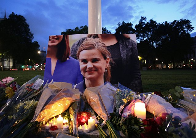 Floral tributes and candles are placed by a picture of slain Labour MP Jo Cox at a vigil in Parliament square in London on June 16, 2016.