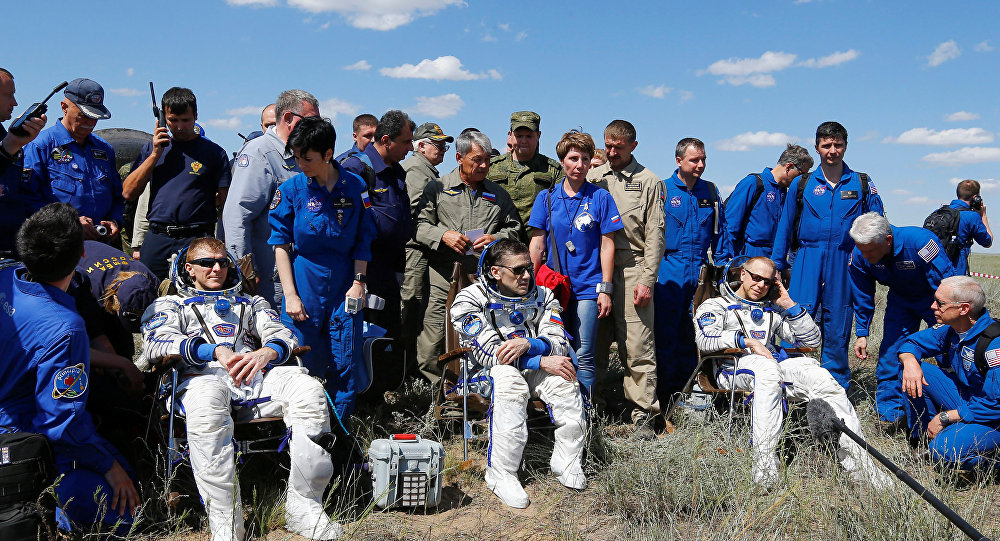 The International Space Station (ISS) crew members Timothy Peake of Britain, Yuri Malenchenko of Russia and Timothy Kopra of the U.S., surrounded by ground personnel, rest shortly after landing near the town of Dzhezkazgan (Zhezkazgan), Kazakhstan, June 18, 2016