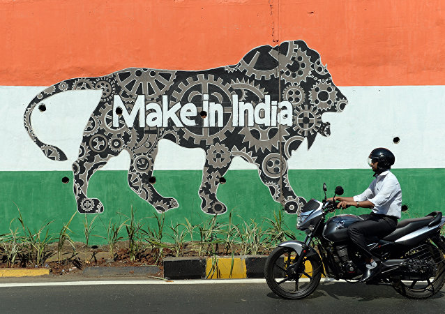 This file photograph taken on February 12, 2016 shows an Indian motorist riding past a wall bearing the image of the mascot for 'Make in India Week' in Mumbai