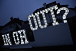 An illuminated In or Out sign is pictured outside a house in Hangleton near Brighton in southern England, on June 23, 2016, as Britain holds a referendum on whether to stay or leave the European Union (EU)