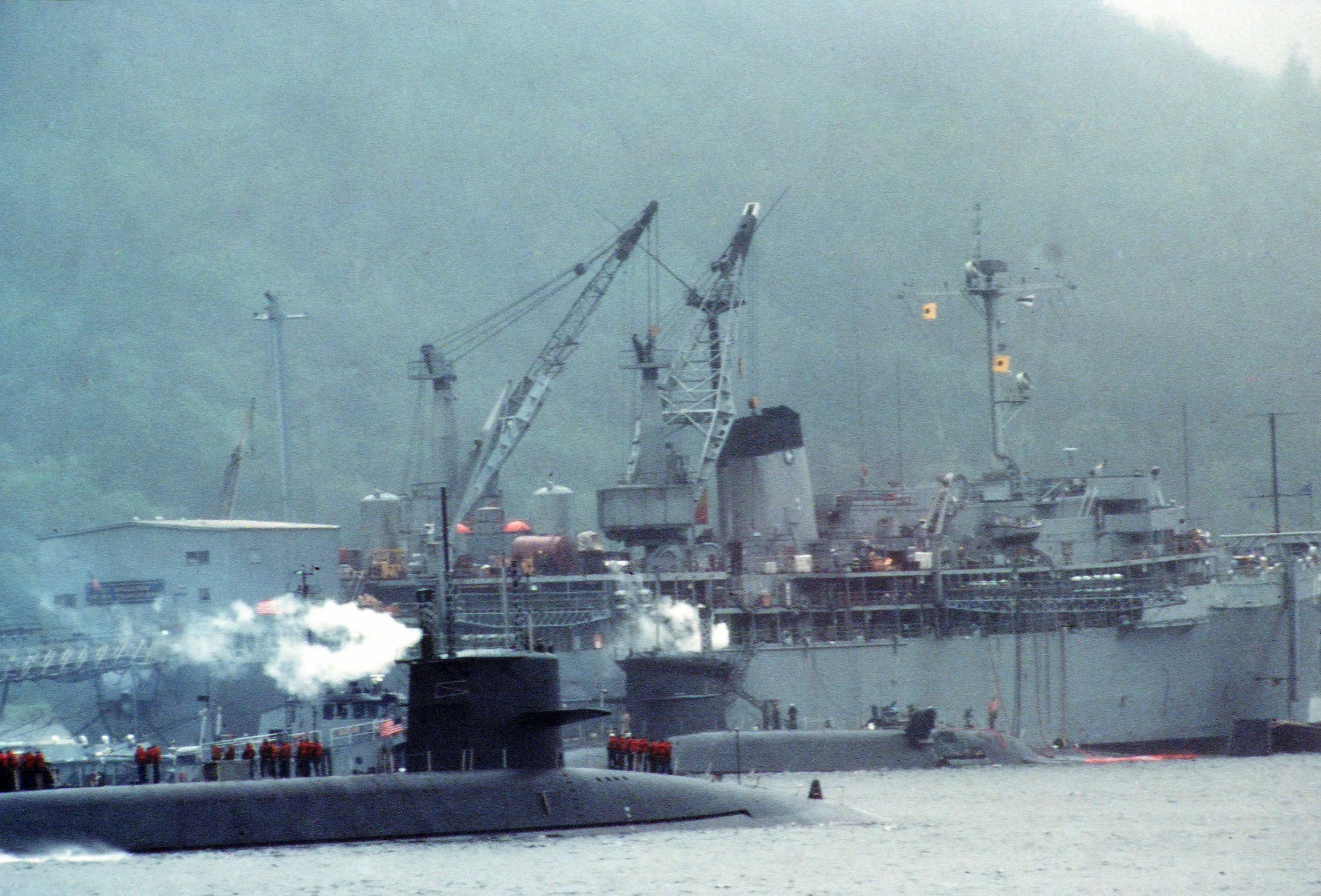 Two U.S. Navy submarines alongside the fleet ballistic missile submarine tender USS Hunley (AS-31) at Navy Fleet Ballistic Submarine Refit Site 1 at Holy Loch, Scotland (UK), 1 December 1985