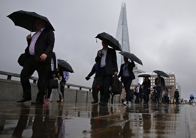 Commuters heading into the City of London walk in the rain across London Bridge, in front of the Shard skyscraper, in central London on June 27, 2016