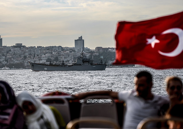 A Turkish flag flies on a ferry as Russian warship the BSF Saratov 150 sails through the Bosphorus off Istanbul en route to the eastern Mediterranean sea on September 26, 2015