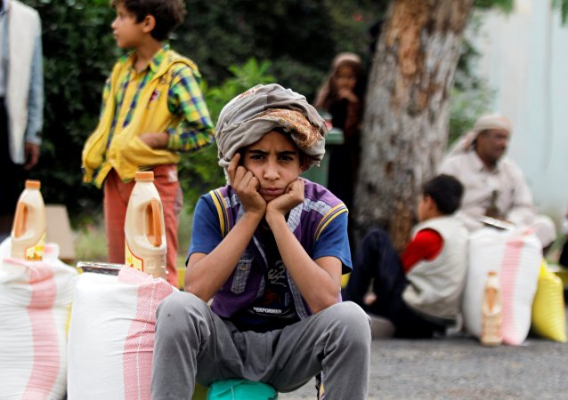 A boy sits next to food supplies he received from a local charity in Sanaa, Yemen, June 23, 2016.