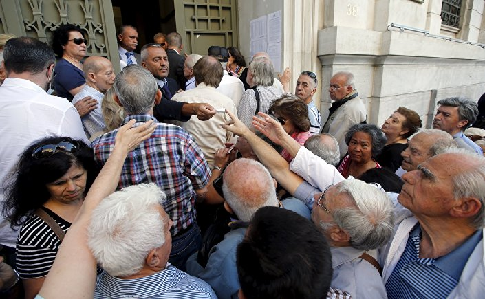 A staff member distributes priority tickets to pensioners outside a National Bank branch in Athens, Greece, July 1, 2015.