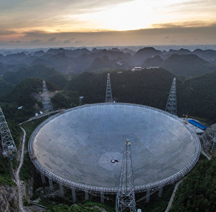 In this photo released by China's Xinhua News Agency, the sun sets above the Five-hundred-meter Aperture Spherical Telescope (FAST) in Pingtang County in southwestern China's Guizhou Province Monday, June 27, 2016