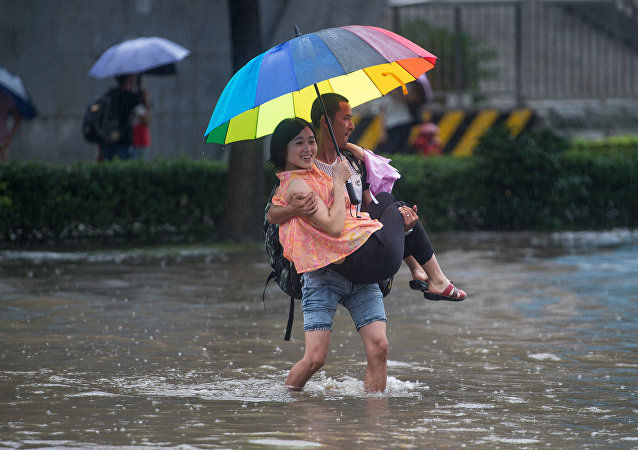 This picture taken on July 2, 2016 shows people crossing a flooded street in Wuhan, in China's central Hubei province
