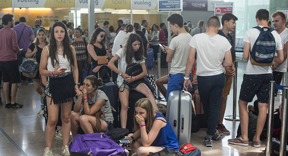 Passengers queue in front of Spanish low-cost airline Vueling check-in counters at the El Prat Airport in Barcelona on July 5, 2016