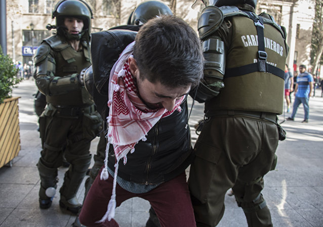 A student demanding the government to speed up a long-awaited reform to guarantee universal access to free public education in Chile, is arrested by riot police during clashed in Santiago on July 5, 2016.