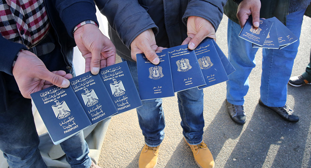 Migrants show passports from Iraqi and Syrian fellow travellers they have to present to buy ferry tickets for their passage to Sweden (photo used for illustration purpose)