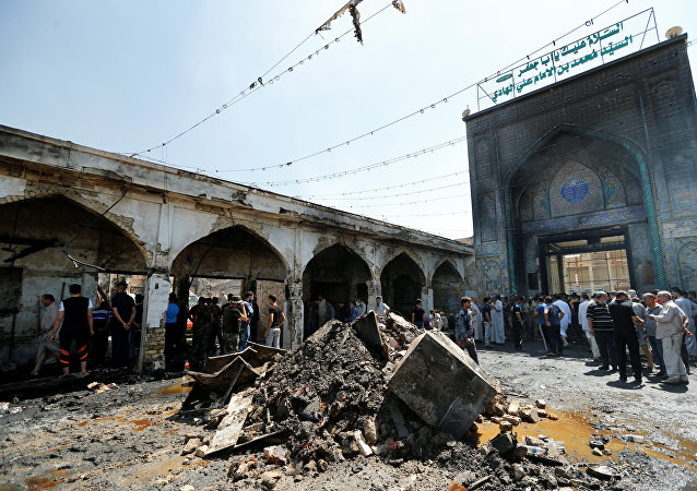 People gather at the site of a suicide attack at the entrance of the Shi'ite Mausoleum of Sayid Mohammed bin Ali al-Hadi in Balad, north of Baghdad, Iraq, July 8, 2016.