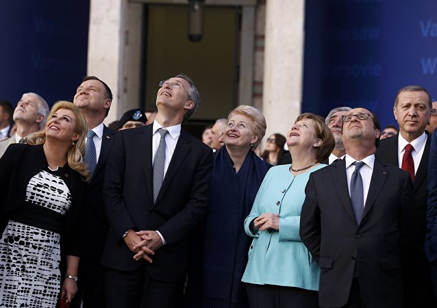 Croatia's President Kolinda Grabar-Kitarovic, Poland's President Andrzej Duda, NATO Secretary-General Jens Stoltenberg, Lithuania's President Dalia Grybauskaite, German Chancellor Angela Merkel, France's President Francois Hollande and Turkey's President Tayyip Erdogan react as they observe a fly past during the NATO Summit in Warsaw, Poland July 8, 2016.