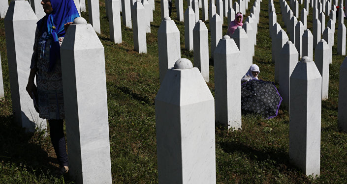 A Bosnian woman prays next to a coffin containing the remains of her relative perished in the Srebrenica massacre, during a funeral ceremony for the 127 victims at the Potocari memorial complex near Srebrenica, 150 kilometers (94 miles) northeast of Sarajevo, Bosnia and Herzegovina, Monday, July 11, 2016