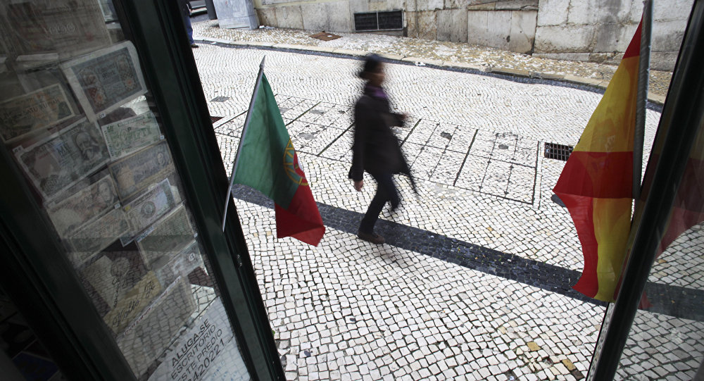 A woman walks past a coin collectors' shop with the flags of Spain and Portugal (File)