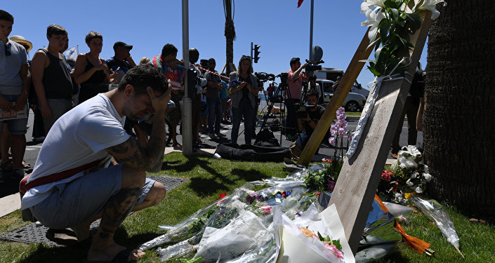 A man kneels and holds his head on July 15, 2016 in front of flowers placed near the site in Nice where a gunman smashed a truck into a crowd of revellers celebrating Bastille Day, killing at least 84 people.