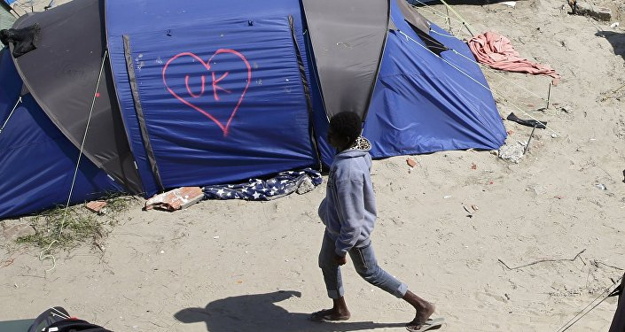 A heart and UK symbol are marked on the side of a tent as a migrant walks in the make-shift camp, called the jungle, in Calais, France, after Britain's referendum results to leave the European Union were announced June 24, 2016.