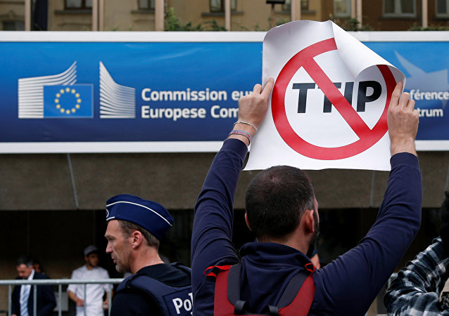 A demonstrator holds a sign during a protest outside a congress centre where negotiators are expected to discuss the 14th Round of the Transatlantic Trade and Investment Partnership (TTIP) in Brussels, Belgium, July 12, 2016.
