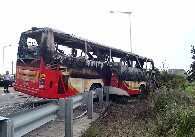 Investigators inspect a bus carrying tourists from mainland China that crashed and caught fire along an expressway on its way to the airport in Taiwan's city of Taoyuan on July 19, 2016