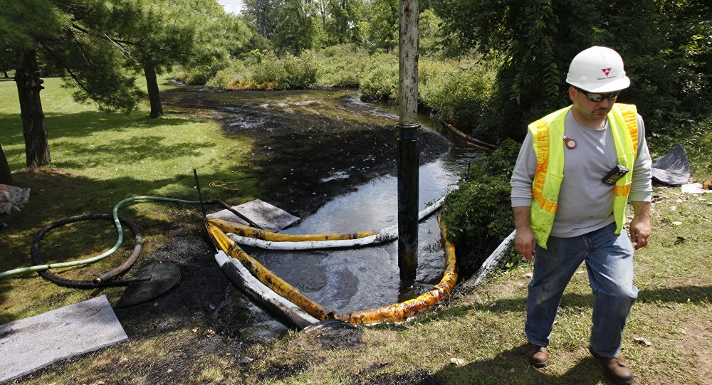 In this July 29, 2010 file photo, a worker monitors the water in Talmadge Creek in Marshall Township, Mich., near the Kalamazoo River as oil from a ruptured pipeline, owned by Enbridge Inc, is vacuumed out the water