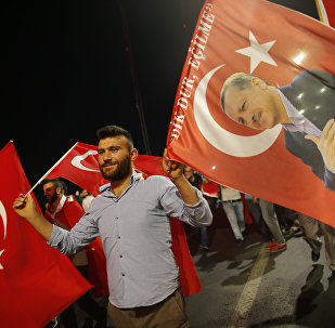 A pro-government supporter waves a Turkish flag and one with the picture of Turkey's President Recep Tayyip Erdogan, right, during a rally on the road leading to Istanbul's iconic Bosporus Bridge, Thursday, July 21, 2016