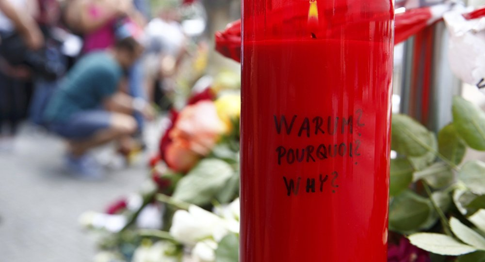 A candle with the words 'Why?' written upon it is placed next to flowers near the Olympia shopping mall, where yesterday's shooting rampage started, in Munich, Germany July 23, 2016.
