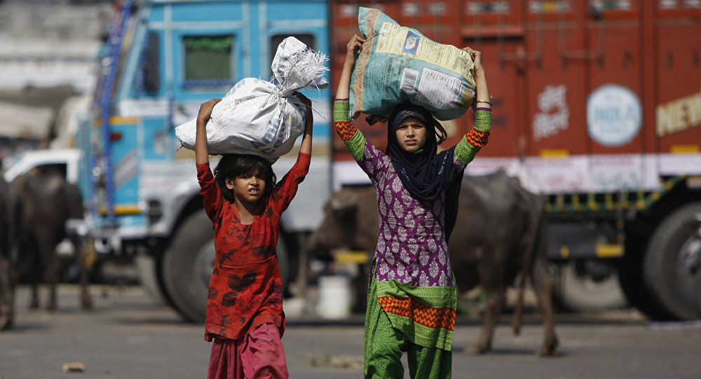 Indian child laborers carry sacks of vegetable leftovers collected from a wholesale market to be sold in their shantytown, on the World Day against Child Labor, on the outskirts of Jammu, India (File)