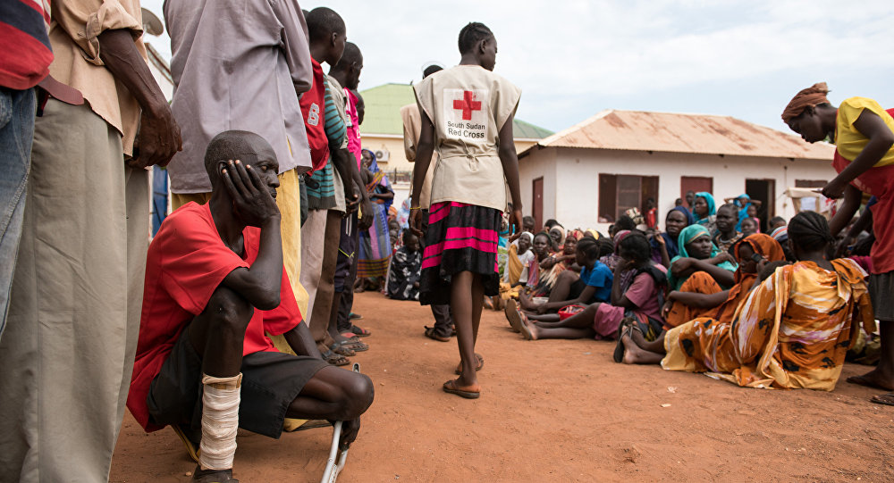 This photo taken on July 1, 2016 shows men and women waiting to be registered as displaced persons in a South Sudan Redcross compound in Wau, South Sudan