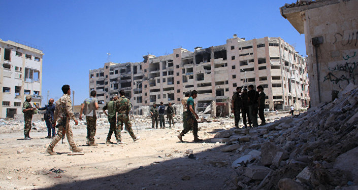 Syrian army soldiers patrol the area around the entrance of Bani Zeid after taking control of the previously rebel-held district of Leramun, on the northwest outskirts of Aleppo, on July 28, 2016