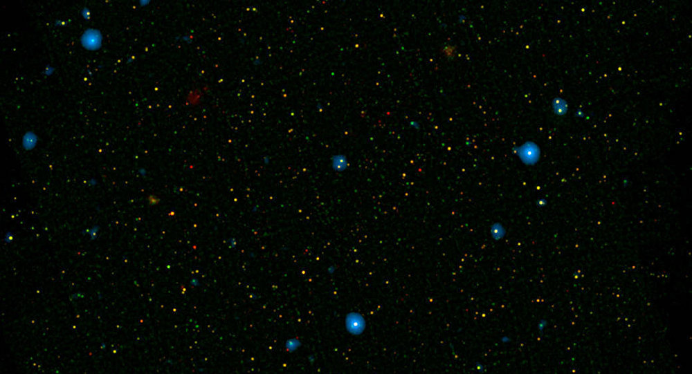 The blue dots in this field of galaxies, known as the COSMOS field, show galaxies that contain supermassive black holes emitting high-energy X-rays