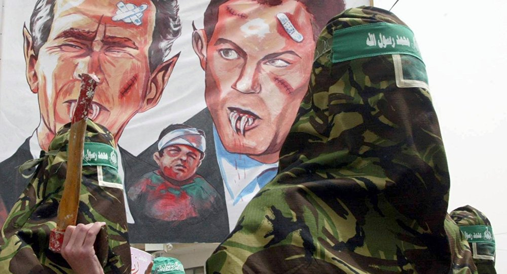 Masked Palestinian members of the Islamic militant group Hamas, march with a larger banner showing a fanged US President George W. Bush (L) and a similar depiction of British Prime Minister Tony Blair during an anti-war protest in the Nusairat refugee camp 04 April 2003, in the Gaza Strip.